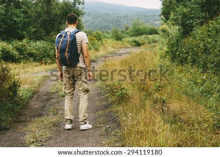 Hiker young man with backpack walking on footpath in summer forest - stock photo