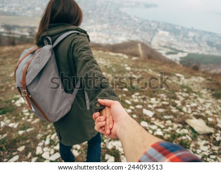 Hiker young woman holding man's hand and leading him on nature outdoor. Couple in love. Point of view shot. Focus on hands.