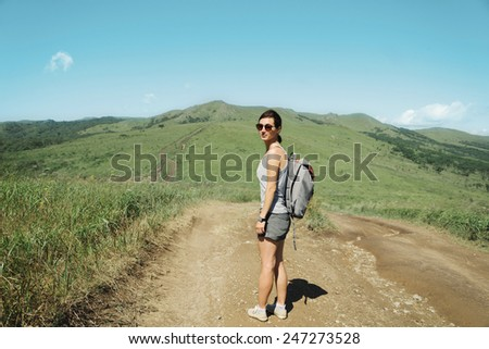 Hiker young woman in sunglasses with backpack walking on footpath in valley among summer mountains - stock photo