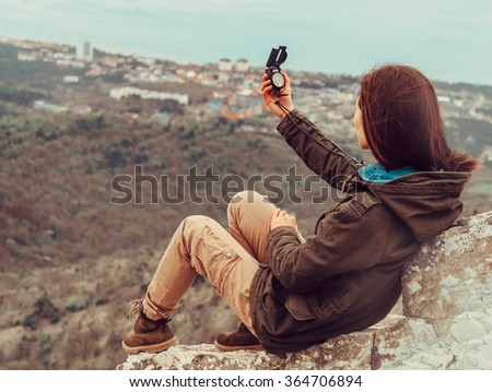 Hiker young woman sitting in the mountains and searching direction with a compass outdoor - stock photo