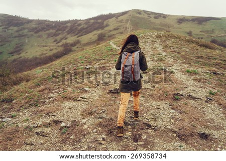 Hiker young woman with backpack climbing on mountain - stock photo