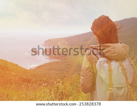 Hiker young woman with backpack looking into distance to the island in summer. Image with sunlight effect - stock photo