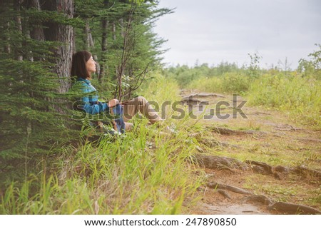 Hiker young woman with backpack resting near the tree in summer forest - stock photo