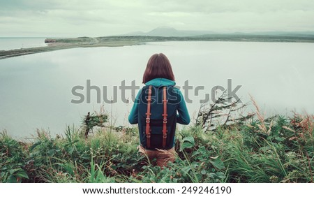 Hiker young woman with backpack standing on hill and enjoying of lake view - stock photo