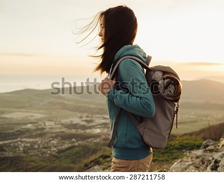 Hiker young woman with backpack standing on peak of mountain in summer at sunset - stock photo