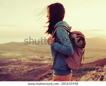 Hiker young woman with backpack standing on peak of mountain in summer at sunset. Image with instagram color effect