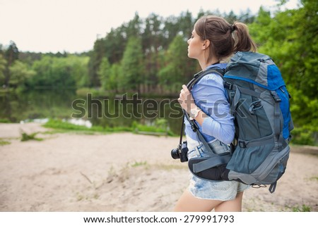 Hiker young woman with backpack standing on shore and enjoying of lake view.