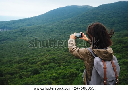 Hiker young woman with backpack taking photographs the beautiful landscape of mountain in summer