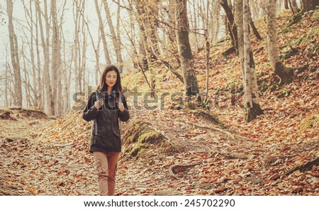 Hiker young woman with backpack walking in late season autumn forest - stock photo