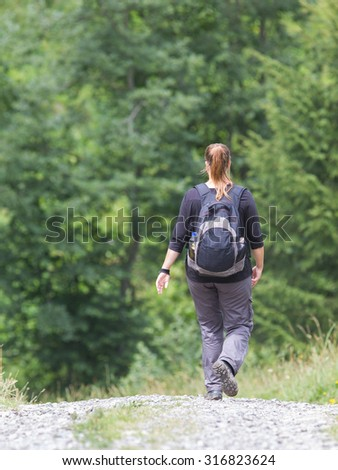 Hiker, young woman with backpack walking on footpath, Switzerland
