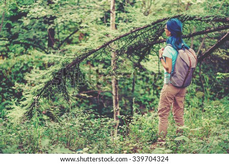 Hiker young woman with blue hair walking in summer forest