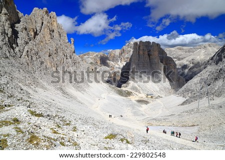 Hikers and climbers in a row descending towards Vajolet towers on rocky trail, Catinaccio massif, Dolomite Alps, Italy - stock photo