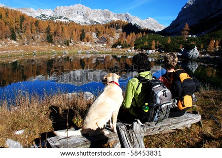 Hikers and dog by the mountain lake - stock photo