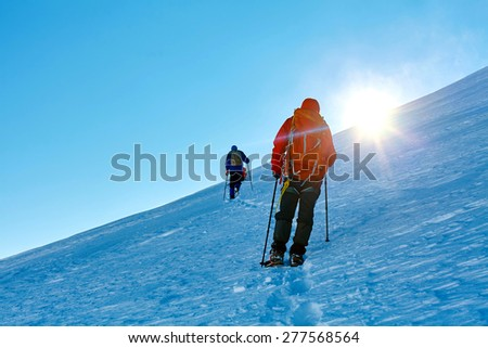 hikers at the top of a pass with backpacks meeting the sunrise in the mountains