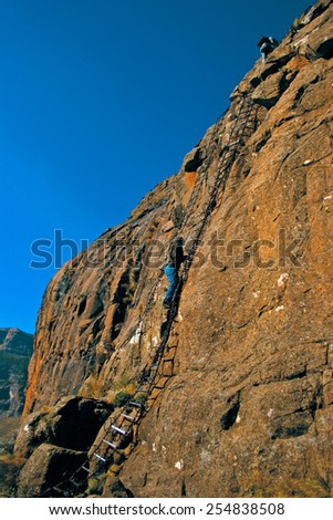 Hikers climb up a set of chain ladders on the side of a cliff on their way up to the top of The Amphitheater in the Drakensberg Mountain range, a Unesco World Heritage Site in South Africa. - stock photo