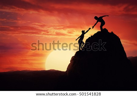 Hikers climbing on rock, mountain at sunset, one of them giving hand and helping to climb. Friendly assistance and support  in a dangerous situation.