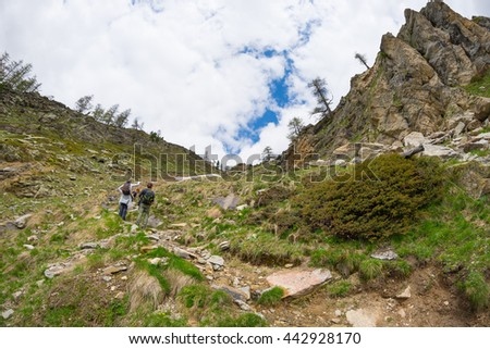 Hikers climbing uphill on steep rocky mountain trail. Summer adventures and exploration on the Alps. Dramatic sky with storm clouds. - stock photo