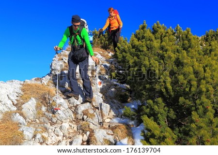 Hikers descend limestone trail under the blue sly on the mountain - stock photo