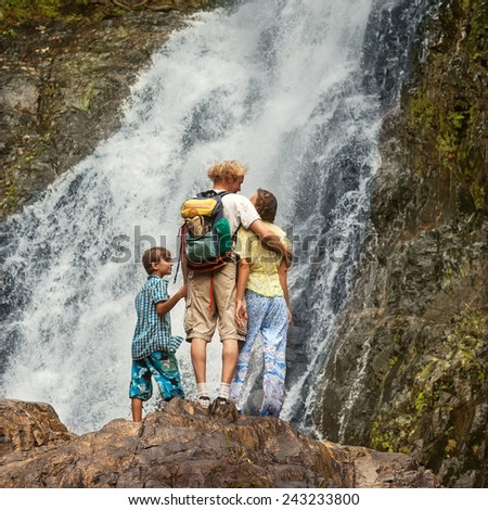 Hikers family looking at a waterfall in the mountains of Thailand - stock photo