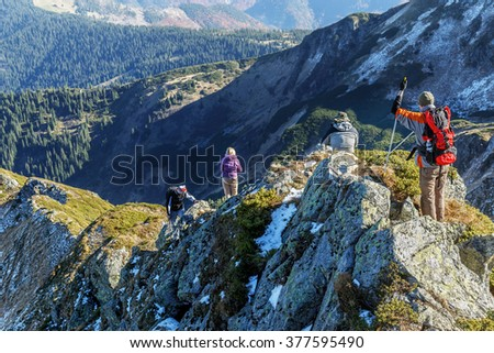 hikers go along mountain ridge - stock photo