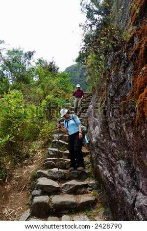 Hikers going up the steep Inca Trail - stock photo