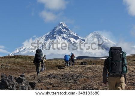 Hikers group trekking in Kamchatka mountain on background of Klyuchevskaya group of volcanoes: Kamen, active Klyuchevskoi Volcano, active Bezymianny Volcano. Russia, Far East, Kamchatka Peninsula. - stock photo