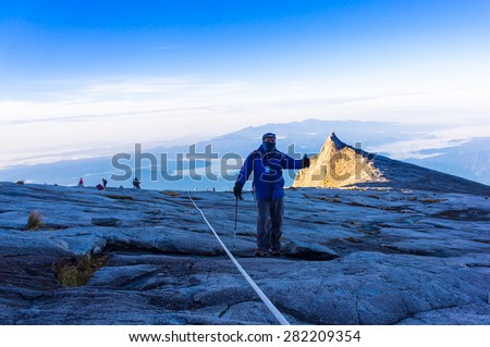 Hikers hiking Mount Kinabalu at early morning. Hiking in view of low light condition. - stock photo