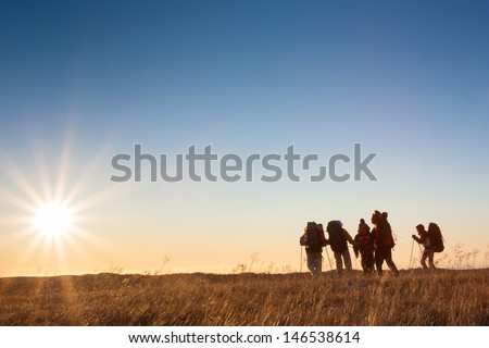 Hikers is walking on plateau in Crimea mountains during sunset - stock photo