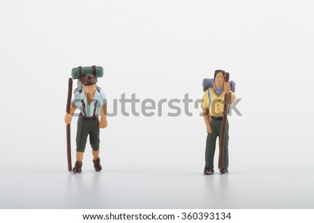hikers miniatures walking on a white background - stock photo