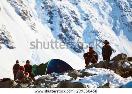 hikers near the tent in the  mountains. Altay, Beluha mount region, Russia.