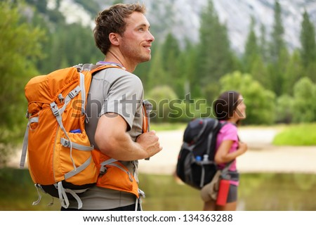 Hikers - people hiking, man looking at mountain nature landscape scenic with woman in background. Happy multicultural young couple in Yosemite National Park, California, USA - stock photo