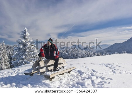 Hikers rest on a small secondary summit in Benediktenwand area in winter
