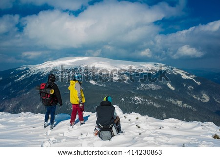 Hikers stand on the top of the mountain admiring the view in Carpathians, Ukraine