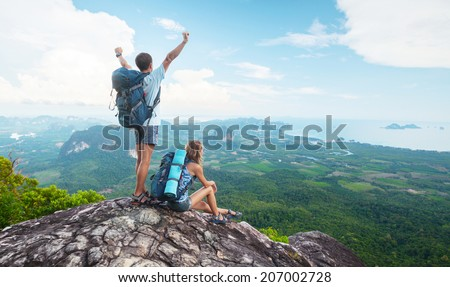 Hikers standing on top of the mountain - stock photo