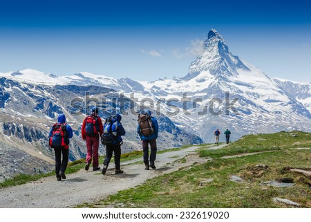 hikers team in the mountains. Matterhorn. Swiss Alps - stock photo
