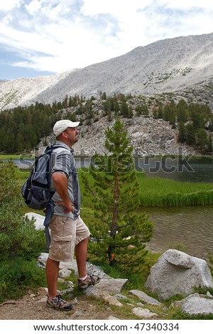Hikers traverse the high country meadows of an alpine range - stock photo
