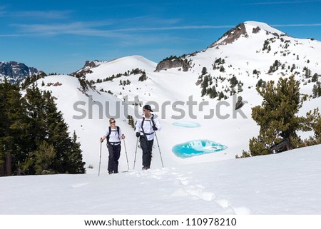 Hikers trek across a snowy mountain landscape - stock photo