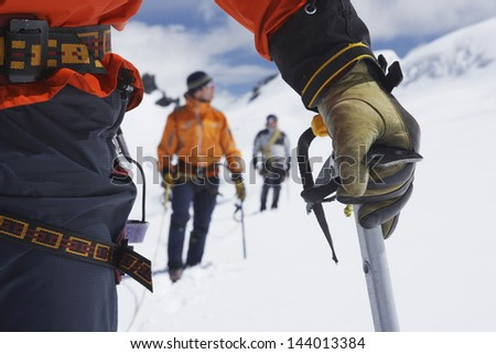 Hikers using walking sticks in snowy mountains with midsection on front man - stock photo