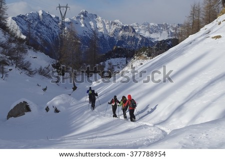 Hikers walking along a track in the snowy mountains. - stock photo