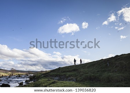 Hikers walking along the River Deveron,Aberdeenshire, Scotland - stock photo