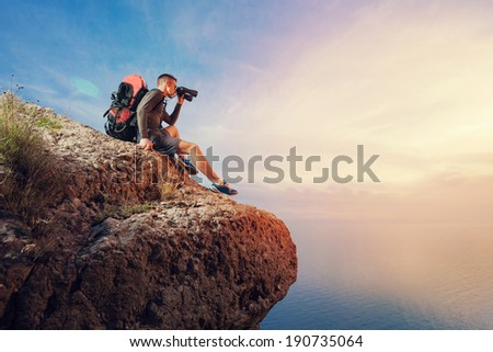 Hikers with backpack and binoculars sitting on top of the mountain and looks into the distance.  - stock photo