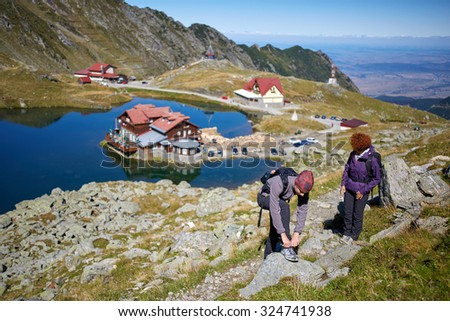 Hikers with backpacks by the lake in the mountains - stock photo