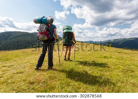 Hikers with backpacks relaxing on top of a mountain and enjoying valley view.