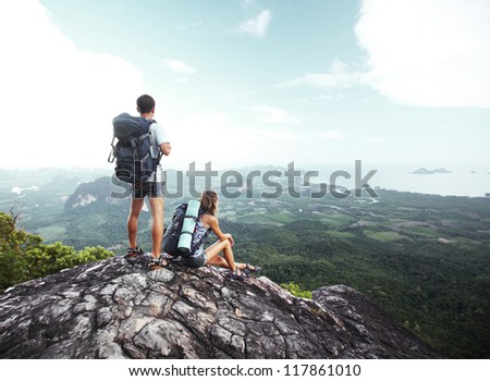 Hikers with backpacks standing on top of a mountain and enjoying a valley view - stock photo