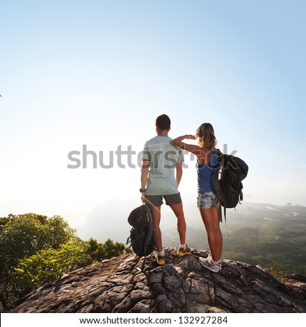 Hikers with backpacks standing on top of a mountain and enjoying sunrise - stock photo