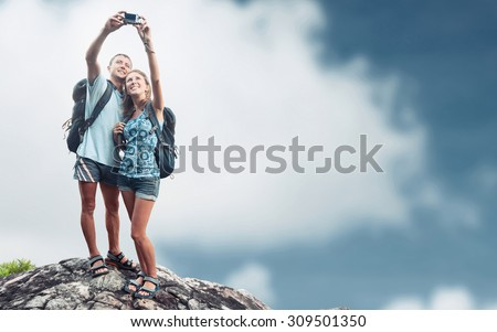 Hikers with backpacks taking selfie on top of the mountain - stock photo