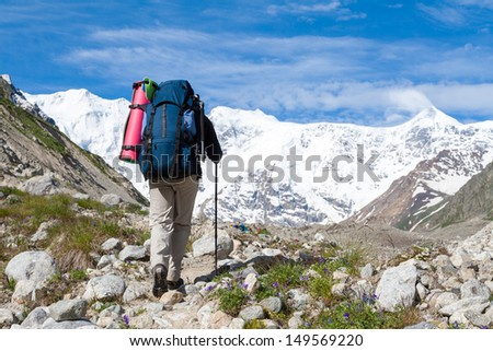 Hikier is approaching wall covered with snow in Caucasus mountains  in Bezengi region, Kabardino-Balkaria, Russia - stock photo