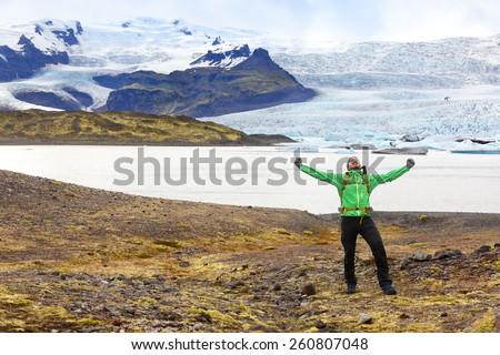 Hiking adventure travel man cheering happy on hike on Iceland. Hiker cheerful at glacier and glacial lagoon / lake of Fjallsarlon, Vatna glacier, Vatnajokull National Park. Icelandic nature landscape. - stock photo