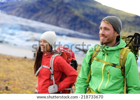 Hiking adventure travel people living active healthy lifestyle wearing jackets and backpacks on Iceland by glacier and glacial lagoon / lake of Fjallsarlon, Vatna glacier, Vatnajokull National Park. - stock photo