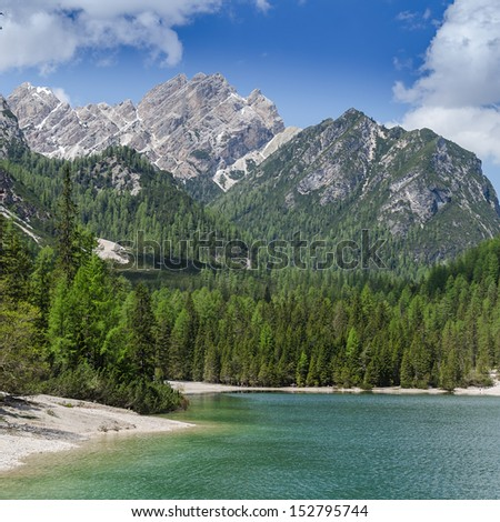 Hiking along the Lago di Braies / Pragser Wildsee on a sunny day in spring - stock photo